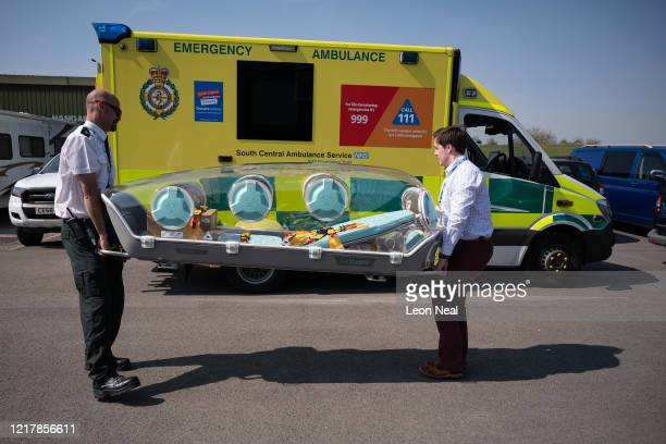An EpiShuttle medical isolation and transportation system by EpiGuard is moved next to an ambulance as members of the UK Armed Forces work with NHS...