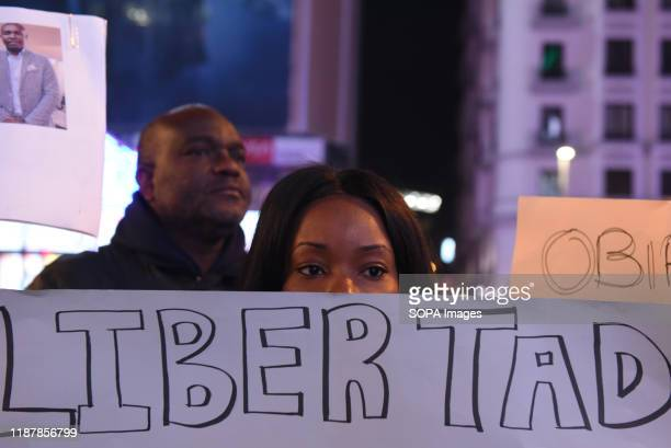 An Equatorial Guinea national holds a placard during the protest Hundreds of people gathered at Callao square in Madrid to mark the International...