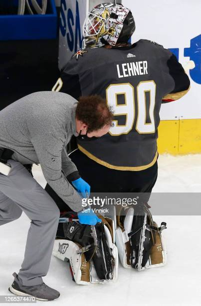 An equipment manager works on the broken skate of Robin Lehner of the Vegas Golden Knights against the Chicago Blackhawks during the second period in...