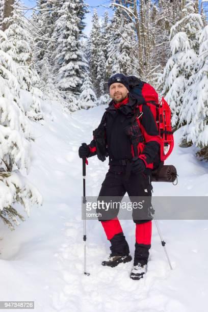 設備の整った男が雪に覆われた木の中で立っています。