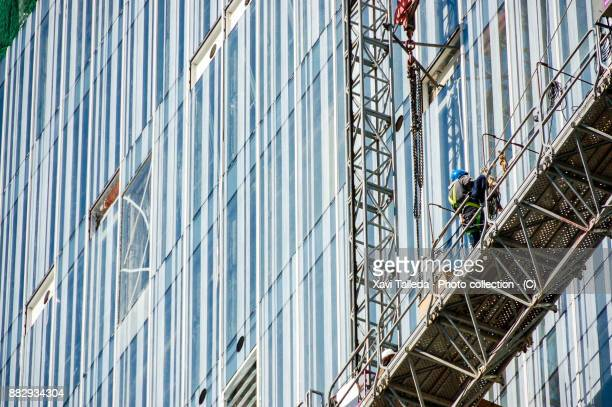 an equipped worker on a scaffold of a crystal skyscraper under construction - bridge built structure stock pictures, royalty-free photos & images