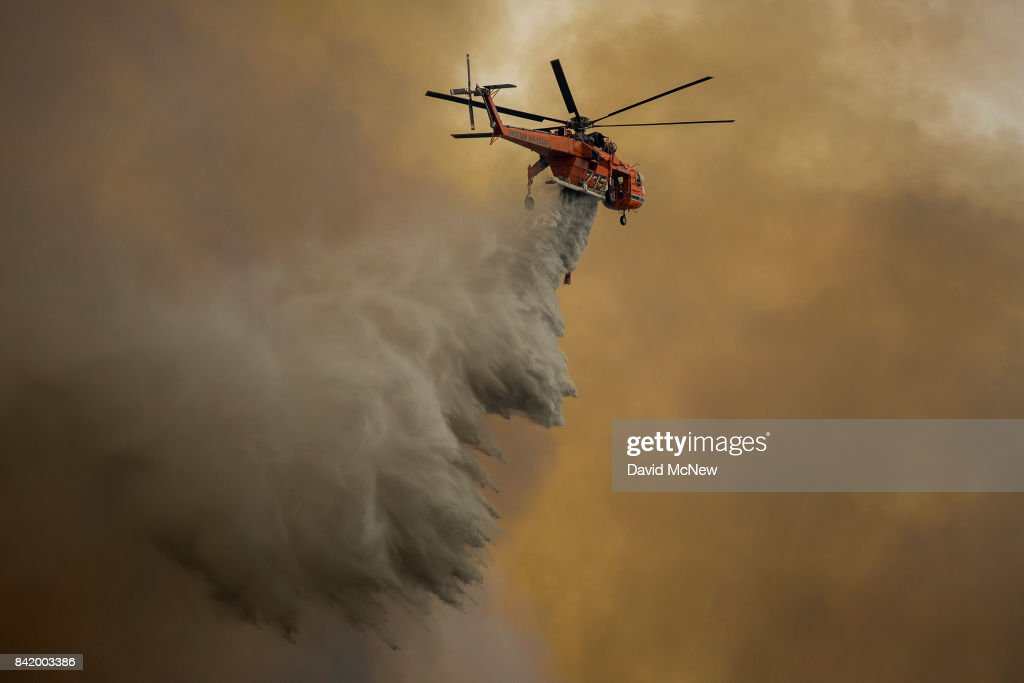 An Erickson Air Crane firefighting helicopter drops water over the La Tuna Fire on September 2, 2017 near Burbank, California. Los Angeles Mayor Eric Garcetti said at a news conference that officials believe the fire, which is at 5,000 acres and growing, is the largest fire ever in L.A. People have been evacuated from hundreds of homes in Sun Valley, Burbank and Glendale. About 100 Los Angles firefighters are expected to return soon from Texas, where they've been helping survivors from Hurricane Harvey.