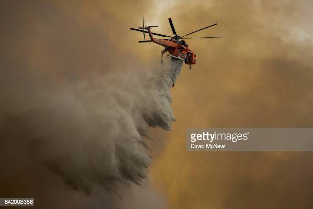 An Erickson Air Crane firefighting helicopter drops water over the La Tuna Fire on September 2 2017 near Burbank California Los Angeles Mayor Eric...