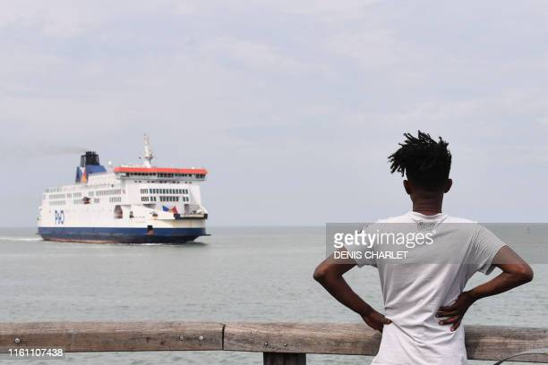 An Eritrean migrant looks at a ferry boat arriving at Calais' harbour from Great Britain on August 04 2019 in Calais