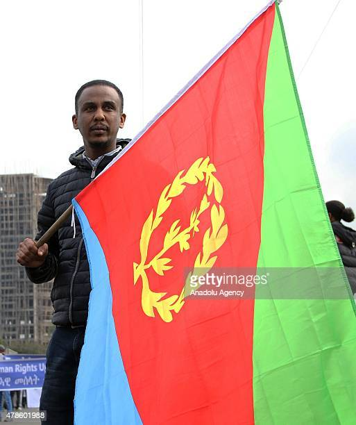 An Eritrean refugee holds an Eritrea flag during a demonstration in front of the African Union headquarters against Eritrean President Isaias...