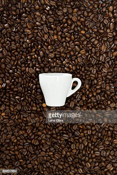 An espresso cup and coffee beans