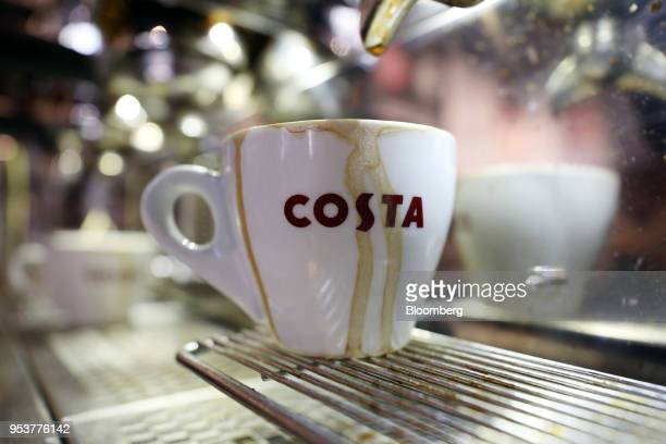 An espresso cup sits on the grille of a coffee making machine in a Costa Coffee shop operated by Whitbread Plc in London UK on Wednesday May 2 2018...