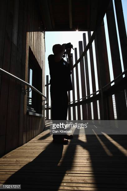An Essex Wildlife Trust Volunteer looks through binoculas over the estuary from the Corey Environmental Trust Visitor Centre at 'Thurrock Thameside...