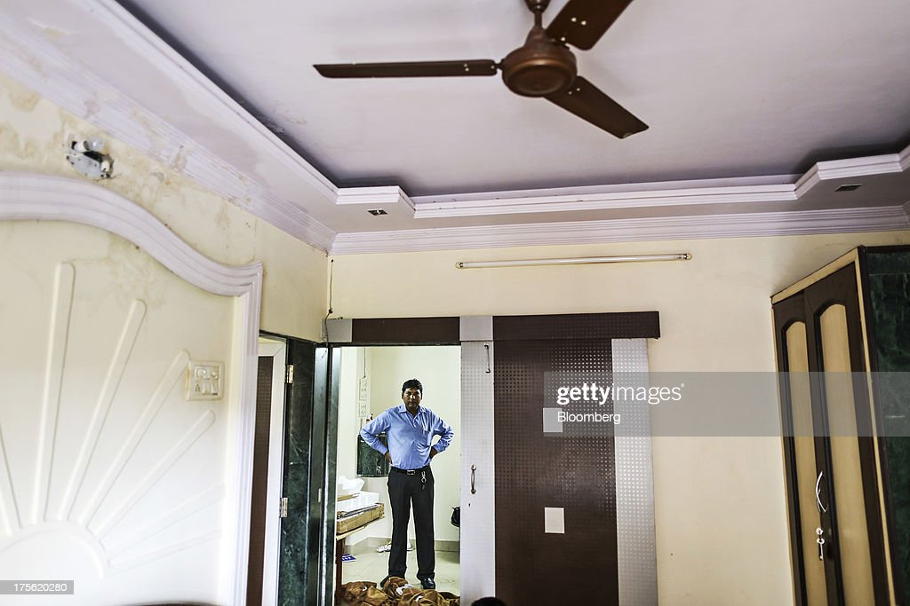 An estate agent is seen through a doorway during an apartment inspection in the Chembur area of Mumbai, India, on Sunday, Aug. 4, 2013. India's purchasing managers index (PMI) for services figures for July are scheduled for release on Aug. 5. Photographer: Dhiraj Singh/Bloomberg via Getty Images