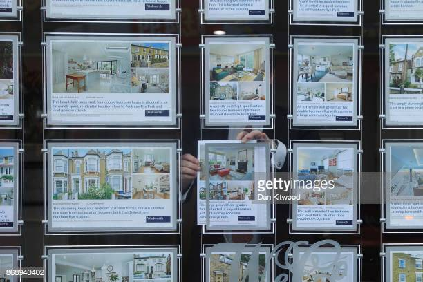An Estate Agent poses inside the display window on November 1 2017 in London England Ahead of an expected interest rate rise the ratings agency...