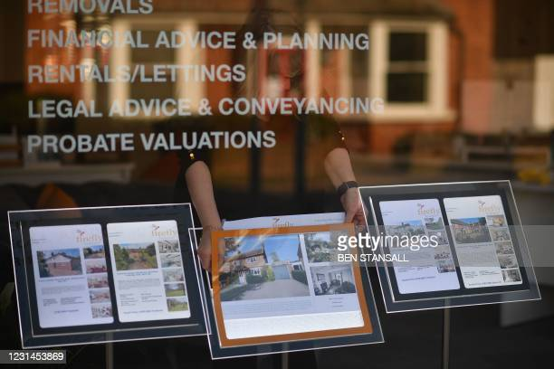 An estate agent re-arranges properties for sale in their window in Paddock Wood, southeast England on March 1, 2021.