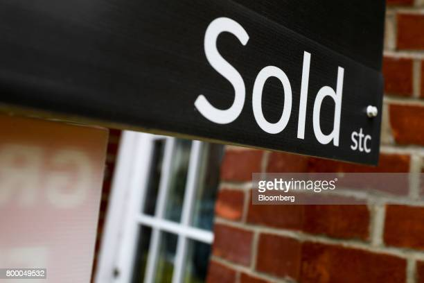 An estate agent's board displaying a 'Sold' property stands outside a house in Chelmsford UK on Thursday June 22 2017 UK house prices recorded their...