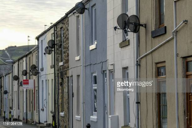 """An estate agent's """"For Sale"""" advertising board stands on a terraced house in Staithes, U.K., on Sunday, Jan. 19, 2020. The fate of one of the Bank of..."""