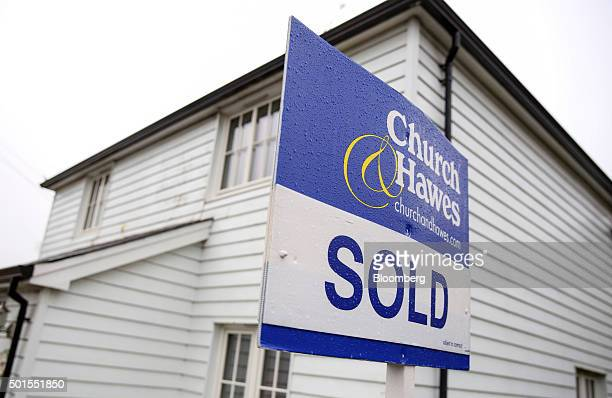 An estate agents sold sign stands outside a cottage in Danbury UK on Tuesday Dec 15 2015 UK asking prices rose an annual 74 percent in December amid...
