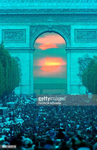 An estimated 200000 people gather on the Champs Elysees in Paris late 10 May 1994 to watch the annular eclipse through the Arch de Triomphe despite...