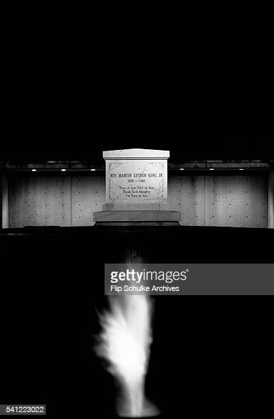 An eternal flame glows in the night in front of Martin Luther King Jr's grave