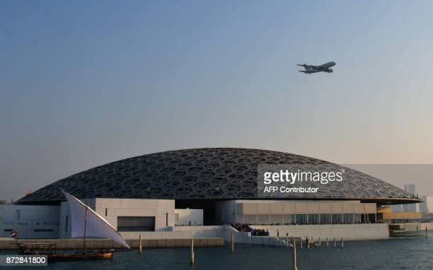 An Ethiad A380 flies over the Louvre Abu Dhabi Museum designed by French architect Jean Nouvel on November 11 2017 during its official opening to the...