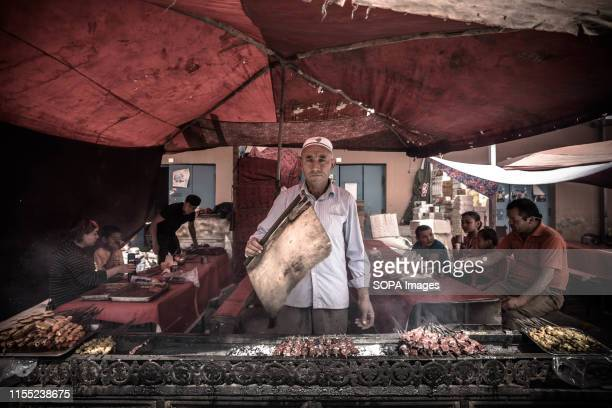 An ethic Uyghur man cooking Kebab in Kashgar bazaar The Xinjiang province is located in the North Western part of China it is the largest province in...