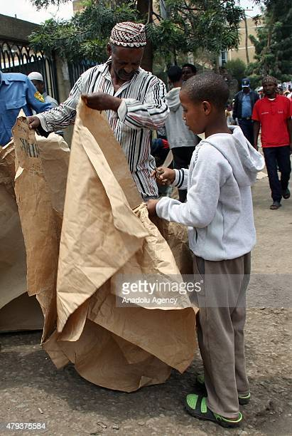 An Ethiopian child vendor sells paper prayer rug to a worshipper at Sumayya Mosque in Addis Ababa Ethiopia on July 03 2015 Ethiopian worshippers lay...