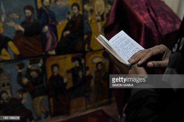 An Ethiopian faithful read the bible before a mass at the St Raphael Coptic Orthodox in Entoto on the outskirts on May 27 2010 of the capital Addis...
