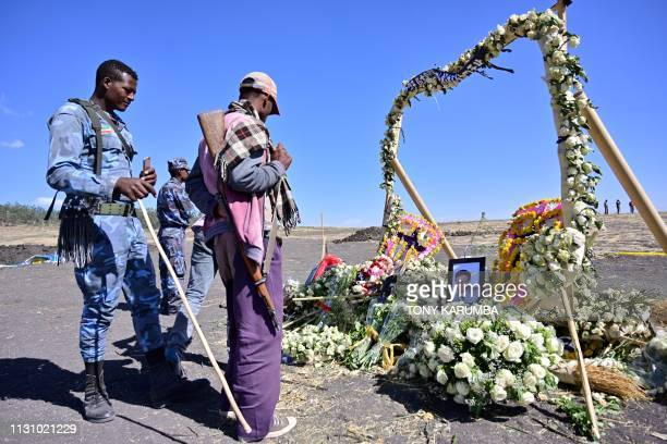 An ethiopian federal policeman and an Oromo tribesman look at a flower memorial bearing potraits of victims at the crash site of an Ethiopian airways...
