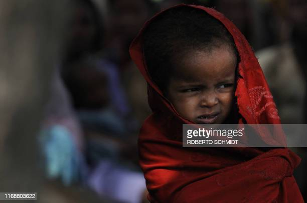 An Ethiopian girl wraps herself in a shawl as she and other members of her family and neighbors line up outside an outpatient medical center run by...