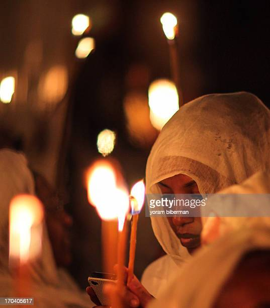 An Ethiopian lady, veiled, holding a smart phone, with candles light around her, at the Light Sunday feast , at the Church of the Holy Sepulchre,...