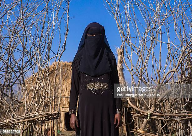 An ethiopian oromo woman dressed in black burqa stands in front of her hut amhara region artuma Ethiopia on February 21 2016 in Artuma Ethiopia