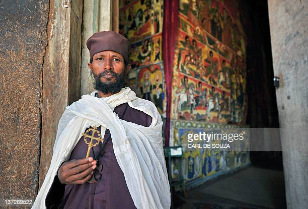 An Ethiopian Orthodox Christian monk poses while holding a cross at Ure Kidane Mihret monestary at Lake Tana in Bahar Dar Ethiopia on January 17 2012...