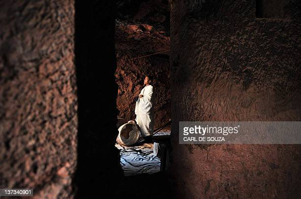 An Ethiopian Orthodox Christian prays before taking part in celebrations for the annual festival of Timkat in Lalibela on January 19 2012 The Timkat...