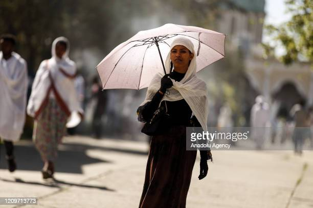 An Ethiopian Orthodox Christian woman holding an umbrella makes her way to attend the Hosanna Day celebrations held a week ahead of the Easter at the...