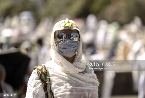 An Ethiopian Orthodox Christian woman wearing a leaf crown made out of date palm and a face mask as a preventive measure against the coronavirus...