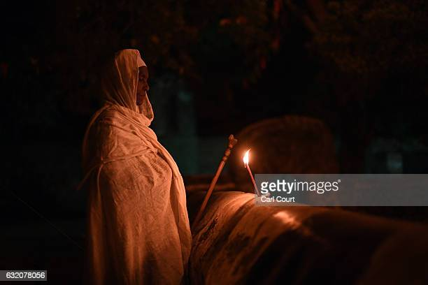 An Ethiopian Orthodox worshipper burns a candle at Fasilides Bath during the annual Timkat epiphany celebration on January 18 2017 in Gondar Ethiopia...
