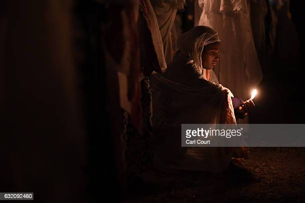 An Ethiopian Orthodox worshipper burns a candle at Fasilides Bath during the annual Timkat epiphany celebration on January 19 2017 in Gondar Ethiopia...