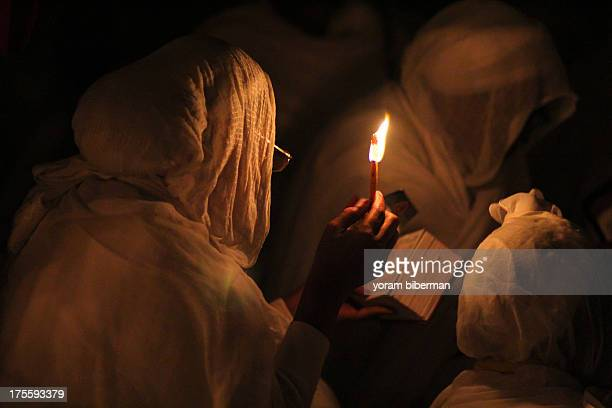 An Ethiopian woman praying at Dier el Sultan at the Light Saturday at night. She is using a candle for lighting.