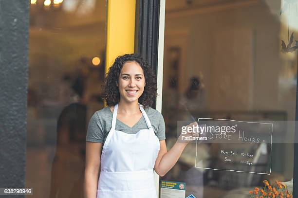 An ethnic adult female business owner is holding a