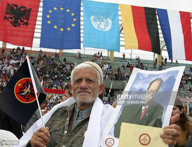 An ethnic Albanian eldery man holds a flag and a portrait of Ibrahim Rugova leader of the main ethnic Albanian party the Democratic League of Kosovo...
