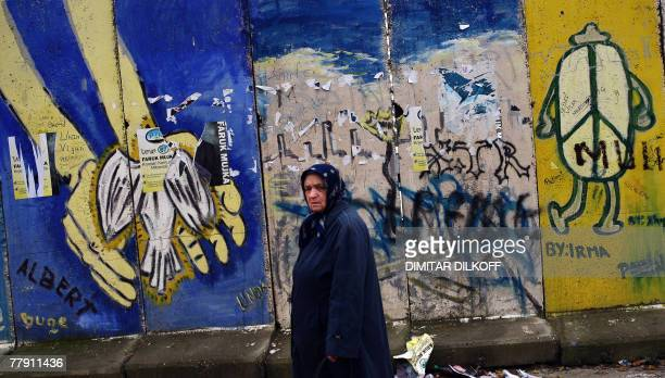 An ethnic Albanian walks past graffiti in the ethnically divided town of Mitrovica 14 November 2007 ahead of the 17 November 2007 general election...