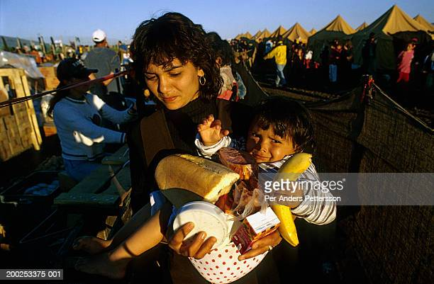 An ethnic Albanian woman and daughter queues for food in a refugee camp in Skopje, Macedonia