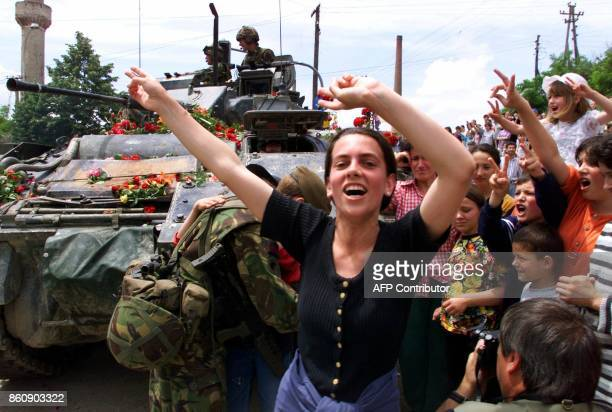 An ethnic Albanian woman celebrates with others in front a British NATO tank in the outskirts of Pristina 13 June 1999 NATO started to send thousands...