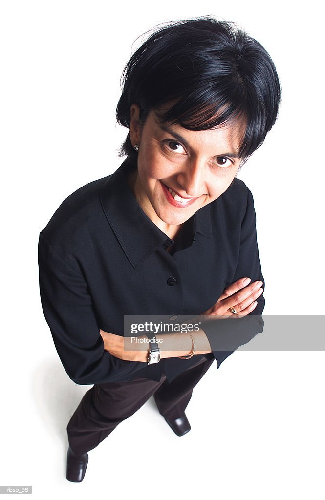 an ethnic business woman dressed in black folds her arms and smiles as she looks up at the camera : Stockfoto