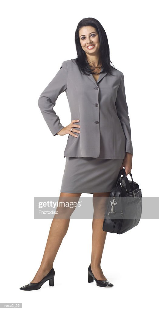 an ethnic business woman in a grey suit holds her computer bag and smiles : Stockfoto