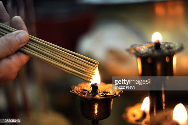 An ethnic Chinese Malaysian burns incense sticks to offer prays during the Hungry Ghost festival in Kuala Lumpur on August 21 2010 In Chinese...