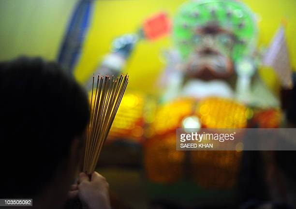 An ethnic Chinese Malaysian holds burning incese while praying during the Hungry Ghost festival in Kuala Lumpur on August 21, 2010. In Chinese...