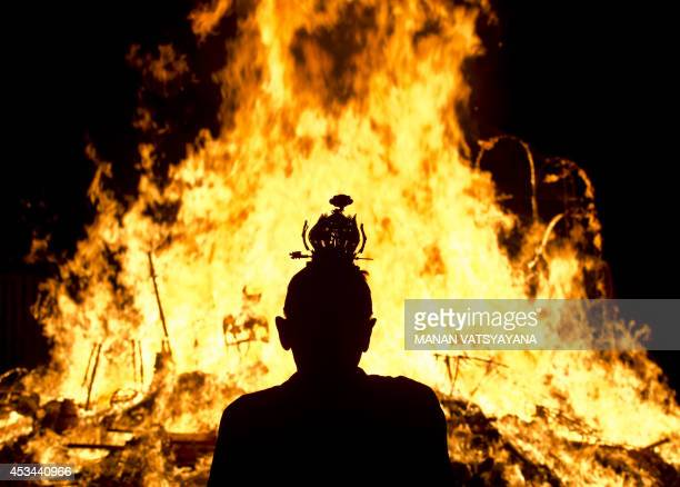 An Ethnic Chinese priest stands in front of statue made of paper of Chinese deity 'Da Shi Ye' or Guardian God of Ghosts set of fire by devotees...