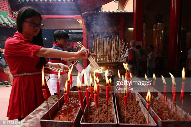 An ethnic Chinese woman burns incense sticks to offer prayers at a temple prior to celebrate the Lantern Festival on the last day of Chinese Lunar...