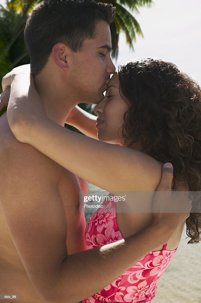 an ethnic couple in swimsuits embrace and kiss as they stand on a beach : Foto de stock