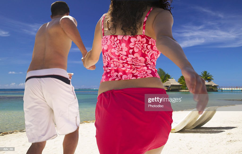 an ethnic couple in swimsuits run along a beautiful beach hand in hand : Foto de stock