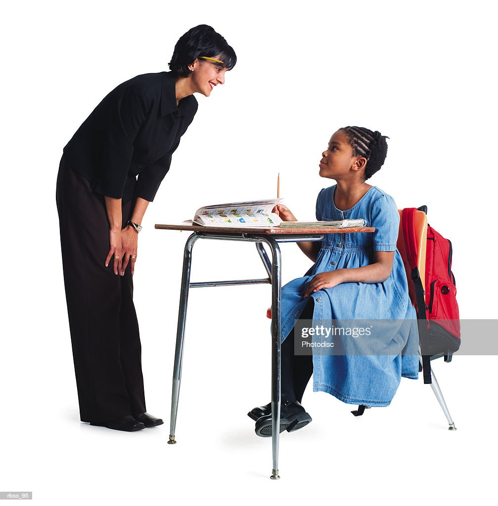 an ethnic female school teacher instructs a young african american girl student at her desk : Foto de stock