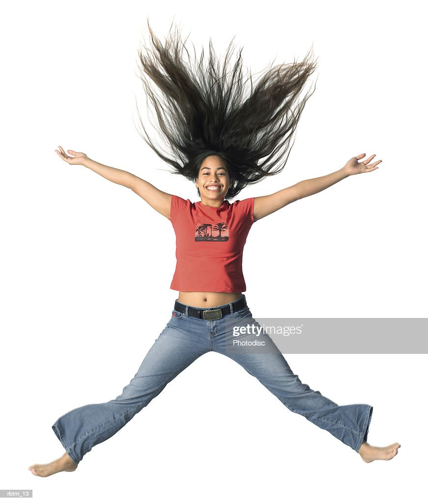 an ethnic female teen in jeans and a red shirt jumps up playfully : Foto de stock